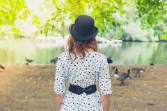 圆顶硬礼帽的妇女由池塘在公园 库存照片
