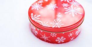 圆,红色曲奇饼和被烘烤的物品铝用白色雪花印刷品样式装饰的罐子容器,基于自然雪 库存图片
