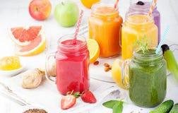 圆滑的人、汁液、饮料、饮料品种用新鲜水果和莓果在白色木背景 图库摄影