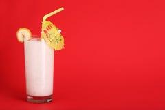 圆滑的人在红色的香蕉味道健康玻璃  免版税库存图片