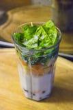 圆滑的人杯子用新鲜水果、菜和牛奶 免版税库存图片
