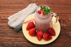 圆滑的人用草莓和牛奶 免版税库存图片