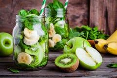 圆滑的人的成份在瓶子:香蕉,猕猴桃,菠菜,绿色苹果 免版税库存图片