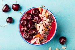 圆滑的人碗用新鲜的黑樱桃、椰子剥落、杏仁和可可粒 顶视图 复制空间 免版税图库摄影