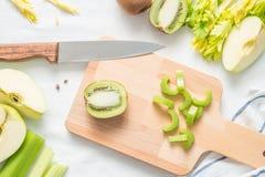圆滑的人,整个和被切的苹果的,在一个木板的切好的芹菜茎未加工的绿色成份在白色布料背景 库存图片