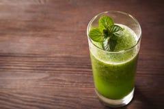 圆滑的人绿化在一张木桌上的饮食素食主义者用薄菏l 免版税库存图片