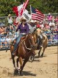 圈地 一个男人和一名妇女有在马背上加拿大和美国的旗子的 库存照片