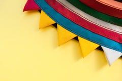 圈子手工制造镶边五颜六色的织品的特写镜头零件与三角边缘的在黄色背景 库存照片
