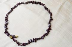 圈子由女性美丽的小珠,棕色黑暗的石头项链做成,琥珀色有米黄织品背景  库存照片