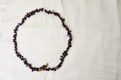 圈子由女性美丽的小珠,棕色黑暗的石头项链做成,琥珀色有米黄织品背景  库存图片