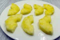 圈子裁减剥了在黄色背景特写镜头的菠萝切片 图库摄影