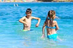 土伦,法国, 2017年8月17日:使用小男孩和的女孩飞溅海水在海滩 免版税库存照片