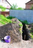 土制沟槽被开掘放置水管 库存照片