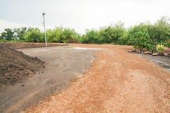 土和泥泞的路在农田 库存照片