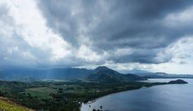 土地和海的风景风景图片深村庄的在弗洛勒斯海岛在多云和大风天期间与太阳光芒是 库存图片