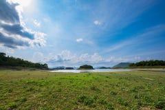土地和草与山和好的天空背景 免版税库存照片
