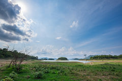 土地和草与山和好的天空背景 免版税库存图片