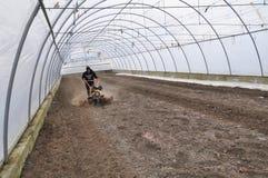 土壤的准备自种植的菜庄稼温室使用一台微型拖拉机 库存图片