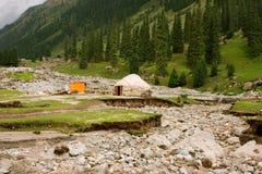 土壤的破坏和中亚农夫的偏僻的家在山森林附近的 免版税库存图片