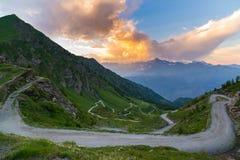 土导致在意大利Colle delle Finestre的高山通行证的山路 在日落,五颜六色的剧烈的天空的Expasive视图, 免版税图库摄影