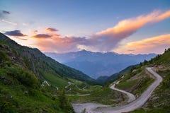 土导致在意大利Colle delle Finestre的高山通行证的山路 在日落,五颜六色的剧烈的天空的Expasive视图, 库存图片