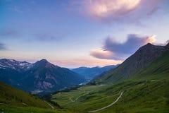 土导致在意大利Colle delle Finestre的高山通行证的山路 在日落,五颜六色的剧烈的天空的Expasive视图, 免版税库存照片