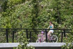 土尔沙俄克拉何马美国5 26 2019母亲和微小的女儿桃红色自行车的茂盛植物围拢的过桥 库存照片