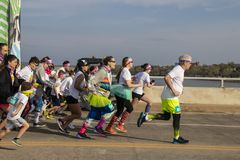 4-6-2019土尔沙美国五颜六色穿戴了第一个赛跑者猛冲在颜色奔跑种族的门外面横跨第21座街道桥梁 库存照片
