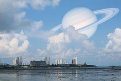 土星支持在海和城市,在地球附近的概念土星的云彩天空 免版税库存照片