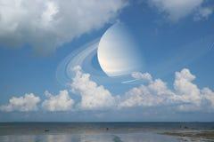 土星支持在海,在地球附近的概念土星的云彩天空 库存图片