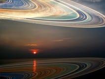 土星环的反射在海和日落的 库存图片