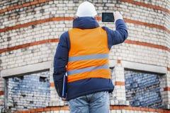 土木工程师在大厦附近拍在片剂个人计算机的照片 库存图片