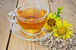 从土木香根的清凉茶与花的 免版税图库摄影