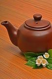 黏土棕色茶壶和茉莉花在木头开花 免版税图库摄影