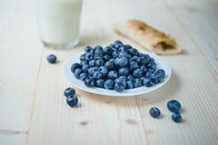 土气健康早餐用蓝莓、小大面包和牛奶在一块玻璃在一张木桌上 杯牛奶用成熟莓果 健康 免版税库存照片