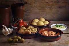 土气党开胃菜例如被烘烤的橄榄,大虾虾,罐 免版税库存图片