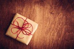 土气减速火箭的礼物,有红色丝带的当前箱子 背景圣诞节关闭红色时间 免版税库存照片