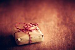 土气减速火箭的礼物,有红色丝带的当前箱子 背景圣诞节关闭红色时间 免版税库存图片