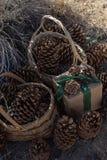 土气包裹圣诞礼物的包装纸,葡萄酒绿色丝带,杉木锥体 库存图片