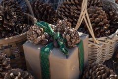 土气包裹圣诞礼物的包装纸,葡萄酒绿色丝带,杉木锥体 库存照片