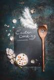 土气复活节烹调与黑板的背景,蛋糕、蛋壳冯quail,木匙子和风信花开花 免版税库存图片