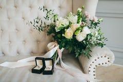 土气婚礼花束和圆环在黑匣子在豪华沙发 户内 附庸风雅 免版税库存图片
