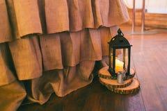 土气婚礼装饰,在木席子的黑灯笼 库存照片