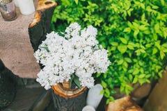 土气婚礼装饰,在树桩的淡紫色安排 库存图片