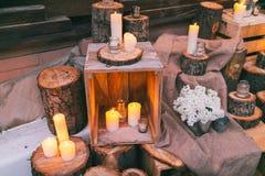 土气婚礼装饰,有蜡烛的装饰的箱子在树桩 库存图片