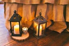 土气婚礼装饰,有蜡烛的黑灯笼在地板上 免版税库存照片