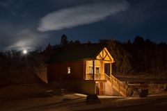 土气客舱在森林在晚上 免版税库存照片