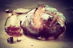 土气家制面包被拍摄在自然光下。葡萄酒作用过程 免版税图库摄影