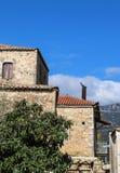 土气岩石大厦在有赤土陶器瓦的海边希腊村庄和金属鸟被紧固在金属火炉管子上- 免版税库存图片