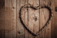 土气心形的分支和黄麻在一张老木桌上 库存图片